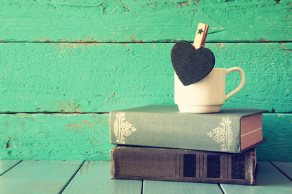 coffee cup with little hart shape blank chalkboard and stack of old books on wooden table. vintage filtered and tones image